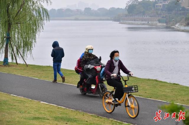 裹上棉袄的外套,今天是武汉有六级大风!明天天气会很好,但最低温度只有2℃。 第2张